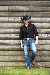 cowboy leaning against a wooden cabin