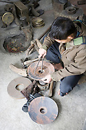 Color film photograph of a Vietnamese worker in a workshop of Dai Bai bronze casting craft village, Bac Ninh Province, Hanoi outskirts, Vietnam, Southeast Asia