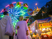 """27 NOVEMBER 2012 - BANGKOK, THAILAND:  Buddhist nuns walk past a ferris wheel spinning in front of Wat Saket during the temple fair in Bangkok. Wat Saket, popularly known as the Golden Mount or """"Phu Khao Thong,"""" is one of the most popular and oldest Buddhist temples in Bangkok. It dates to the Ayutthaya period (roughly 1350-1767 AD) and was renovated extensively when the Siamese fled Ayutthaya and established their new capitol in Bangkok. The temple holds an annual fair in November, the week of the full moon. It's one of the most popular temple fairs in Bangkok. The fair draws people from across Bangkok and spills out in the streets around the temple.   PHOTO BY JACK KURTZ"""