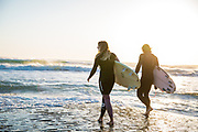 Couple holding surfboards, walking down the slipway into the surf and golden sunlight at St Ouen's Bay, Jersey, Channel Islands
