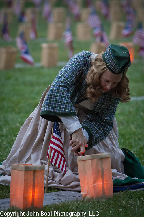 """Civilian reenactors, Lisa Donnelly lights luminarias at the Soldiers National Cemetery, during the Sesquicentennial Anniversary of the Battle of Gettysburg, Pennsylvania on Sunday, June 30, 2013.   Following """"A New Birth of Freedom"""" program at Meade's Headquarters, a procession by candlelight was led to the cemetery. John Boal photography"""
