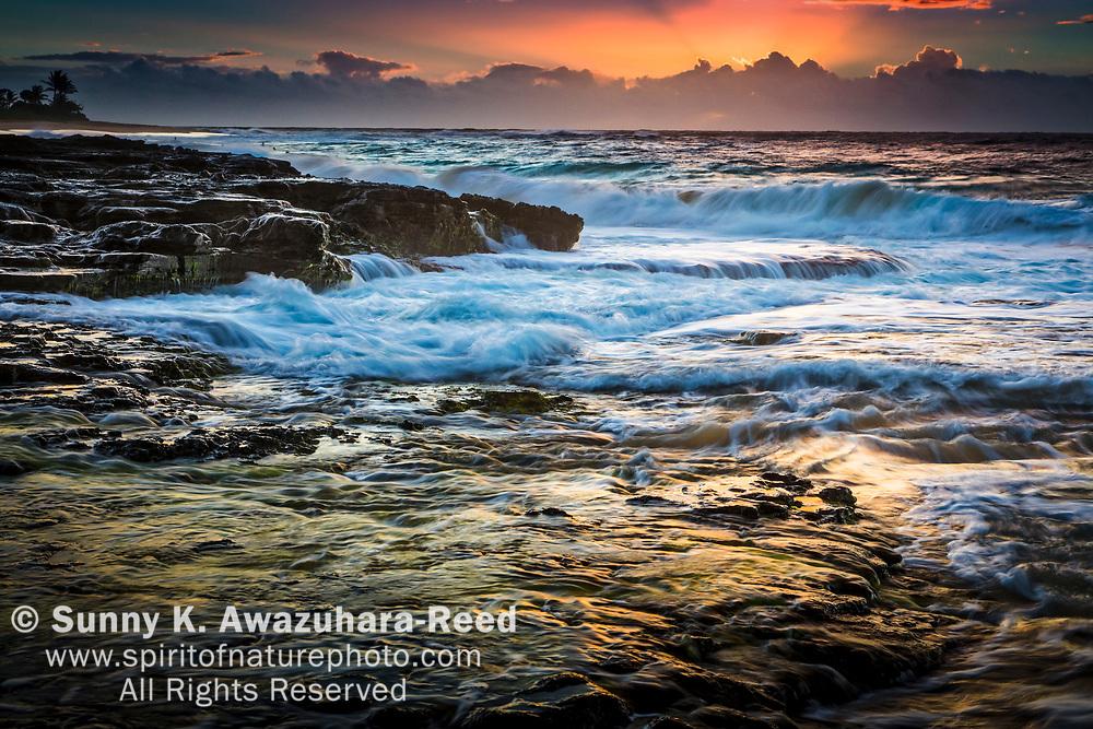 Wave cascading down the rocky shore at sunrise. Rays of sun over horizon. Golden lights on the rock. Sandy Beach. Oahu Island, Hawaii.