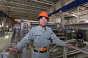 Jiangsu Oji Paper Vice General Manager poses for a photograph in front of the assembly line of Oji Paper Factory, in Nantong, Jiangsu province, China, on May 25, 2010. Photo by Lucas Schifres/Pictobank