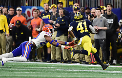 Florida Gators defensive back Jeawon Taylor (29) reaches out for Michigan Wolverines running back Christian Turner (41)during the Chick-fil-A Bowl Game at  the Mercedes-Benz Stadium, Saturday, December 29, 2018, in Atlanta. ( Kyle Hess via Abell Images for Chick-fil-A Kickoff)