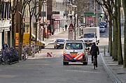 Nederland, Nijmegen, 25-3-2020 Een politieauto, politiebusje, rijdt door het bijna uitgstorven stadscentrum . Om te voorkomen dat groepen mensen dicht bij elkaar komen wordt extra surveillance gehouden . De terrassen zijn afgezet met lint om duidelijk te maken dat daar niet in de zon gezeten mag worden . Foto: Flip Franssen