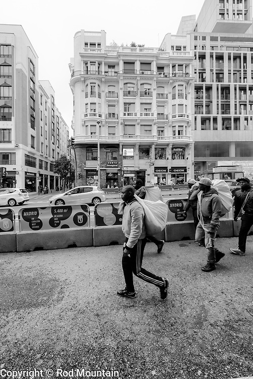 Madrid, Spain - February 15, 2018 - Street vendors walking along Calle Gran Via during the afternoon in Madrid. <br /> <br /> Image: © Rod Mountain<br /> <br /> http://www.rodmountain.com <br /> <br /> Instagram<br /> @spain @visita_madrid<br /> <br /> FaceBook<br /> @spain.info @visitamadridoficial<br /> <br /> Twitter<br /> @spain @Visita_Madrid<br /> <br /> https://www.esmadrid.com/en<br /> <br /> https://en.wikipedia.org/wiki/Madrid<br /> <br /> https://www.spain.info/en/que-quieres/ciudades-pueblos/grandes-ciudades/madrid.html<br /> <br /> #storyofthestreets #timeless_streets #noirstreetlife #capturestreets #streetshared #imaginatones #streettogether #worldbestgram #blackandwhite #excellent_bnw #exploretocreate #featuremeinstagood #illgrammers#instamagazine #bnw_guru #bnw_madrid #enblancoynegro #bnw_city #insta_BWgramers #bnw_society #instatraveling #sharetravelpics #socialdocumentary #traveldocumentary #ourplanetdaily #bwstylesgf #bnw_captures