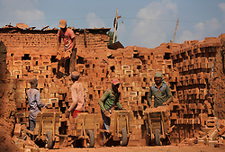 July 24, 2017 - Budgam, Kashmir, India - Migrant laborers load bricks on their handcarts in a brick kiln at a village in Budgam district about 20 km southwest of Srinagar, summer capital of Indian-controlled Kashmir. Indian-controlled Kashmir has more than 300 brick kilns. Environment experts say that the large number of brick kilns near habitations in Indian-controlled Kashmir are posing a serious danger to life and health of people.  (Credit Image: © Javed Dar/Xinhua via ZUMA Wire)
