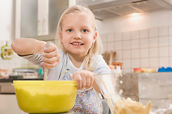 Girl mixing flour in bowl for cookies, smiling, portrait