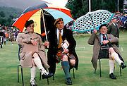 Scottish judges in tartan kilts shelter from rain at the Braemar Royal Highland Gathering, the Braemar Games in Scotland