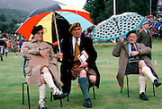 Scottish judges in tartan kilts shelter from rain at the Braemar Royal Highland Gathering, the Braemar Games in Scotland