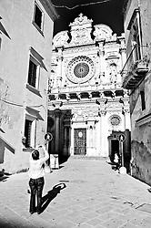 Turista mentre fotografa la Basilica di Santsa Croce a Lecce.