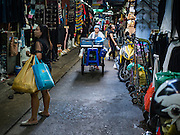 12 JANUARY 2017 - BANGKOK, THAILAND: A food vendor pushes her cart through Bo Bae Market. Bo Bae Market is a sprawling wholesale clothing market in Bangkok. There are reportedly more than 1,200 stalls selling clothes made in Thailand and neighboring countries. Bangkok officials have threatened to shut down parts of Bo Bae market, but so far it has escaped the fate of the other street markets that have been shut down.         PHOTO BY JACK KURTZ