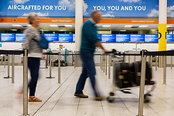 Passengers pass the deserted check-in as travel company Thomas Cook has ceased trading after failing to come to a deal with its bankers and creditors, leaving tens of thousands of travellers unable to depart on their holidays from South Terminal at Gatwick Airport, and a massive repatriation exercise to return holidaymakers from destinations all over the world. London Gatwick Airport, September 23 2019.