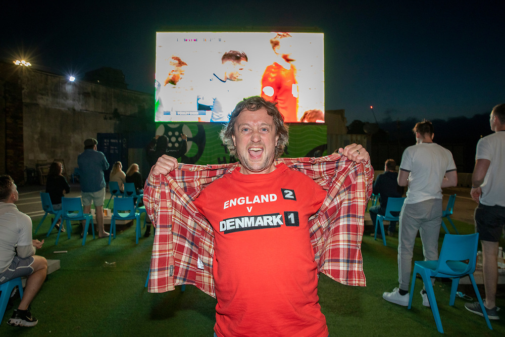 An England fan wearing a 2-1 score prediction on his t-shirt celebrating a goal during the Euro 2020 semi final match between England and Denmark on the 7th of July 2021 at the outdoor screen at Folkestone Harbour Arm, in Folkestone, United Kingdom. (photo by Andrew Aitchison / In pictures via Getty Images)