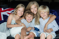 four children smiling and sitting for a portrait at home
