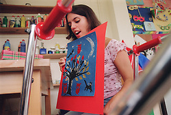 Teenage girl with physical disability holding up finished painting during art lesson in residential respite care home,