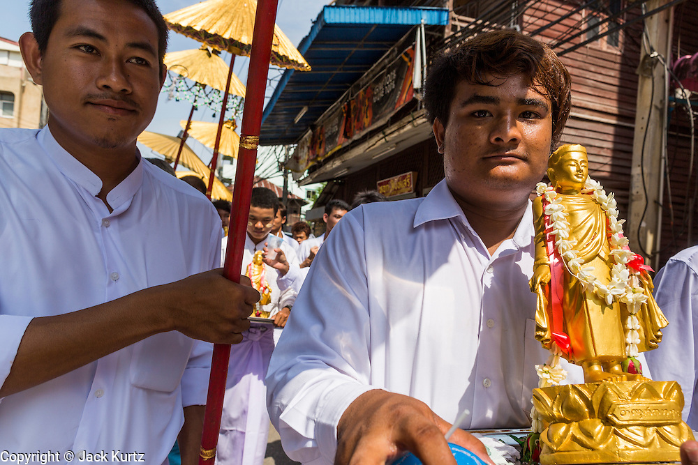 24 MAY 2013 - MAE SOT, THAILAND: Burmese emigres in Mae Sot, Thailand, carry a statue of the Buddha through the city during a procession on Visakha Puja Day. Visakha Puja (Vesak) marks three important events in the Buddha's life: his birth, his attainment of enlightenment and his death. It is celebrated on the full moon of the sixth lunar month, usually in May on the Gregorian calendar. This year it is on May 24 in Thailand and Myanmar. It is celebrated throughout the Buddhist world and is considered one of the holiest Buddhist holidays. Burmese Buddhist in Mae Sot celebrated with a procession through Mae Sot that ended with a service followed by a communal meal at Wat Pha Mai, the most important Burmese Buddhist temple in Mae Sot.    PHOTO BY JACK KURTZ