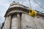 A coil of electrical wiring cables is next to the walls of the Bank of England on Threadneedle Street - part of ongoing alterations to the highway during the Coronavirus pandemic in the City of London, the capitals financial district, on 6th August 2020, in London, England. SRL are the UK's only manufacturer to sell and hire traffic light equipment and their Urban64 product is the first, and only, permanent technology system to be designed uniquely for temporary installations in the U.K. The Urban64 design allows for simple and quick over-head installation, with the ability to replicate the technology provided by the preceding permanent system, and therefore maintaining traffic flow efficiency.