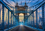 """The John A. Roebling Suspension Bridge spans the Ohio River between Cincinnati, Ohio and Covington, Kentucky. When the first pedestrians crossed on December 1, 1866, it was the longest suspension bridge in the world at 1,057 feet (322 m) main span. Today, many pedestrians use the bridge to get between the arenas in Cincinnati (Paul Brown Stadium, Great American Ball Park, and U.S. Bank Arena) and the hotels, bars, restaurants, and parking lots in Northern Kentucky. The bar and restaurant district at the foot of the bridge on the Kentucky side is known as Roebling Point.<br /> <br /> Ramps were constructed leading directly from the bridge to the Dixie Terminal building used for streetcars. These provided Covington–Cincinnati streetcars """"with a grade-separated route to the center of downtown, and the terminal building was originally intended to connect, via underground pedestrian passages, with the never-built Fountain Square Station of the infamous Cincinnati Subway."""" When streetcar service ceased in the 1950s the terminal was converted to use as a diesel bus terminal. The ramps were removed in 1998 when it ceased being used as a bus terminal."""