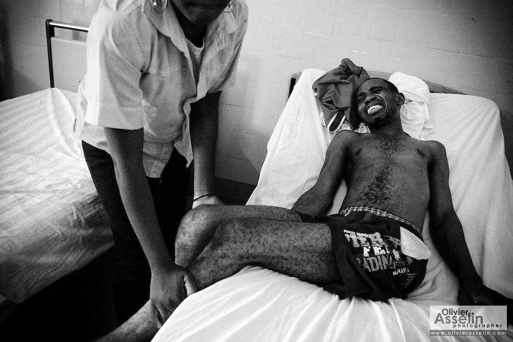 """Tony Boussana, 24, who is partly paralized by polio, is helped by his girlfriend Sabena, 19, as he tries to sit up in his bed at the A. Cisse Hospital in Pointe-Noire, Republic of Congo on Friday December 3, 2010. """"When I got to the hospital I could still move my arms, but now I can't"""", he says. """"I feel completely lost."""""""