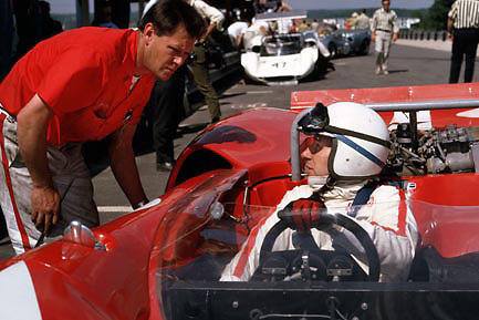 """John Surtees, reigning Can-Am champion of the year before, in new Lola T70 at Elkhart Lake's Road America, the opening round of the 1967 series. Bending over the cockpit is mechanic Malcolm Malone, known as """"Mac,"""" who been Surtees' winning crew chief in '66 (Malone's ID confirmed by his sister, Kath, in February 2015). PHOTO BY Pete Lyons 1967 / www.petelyons.com"""