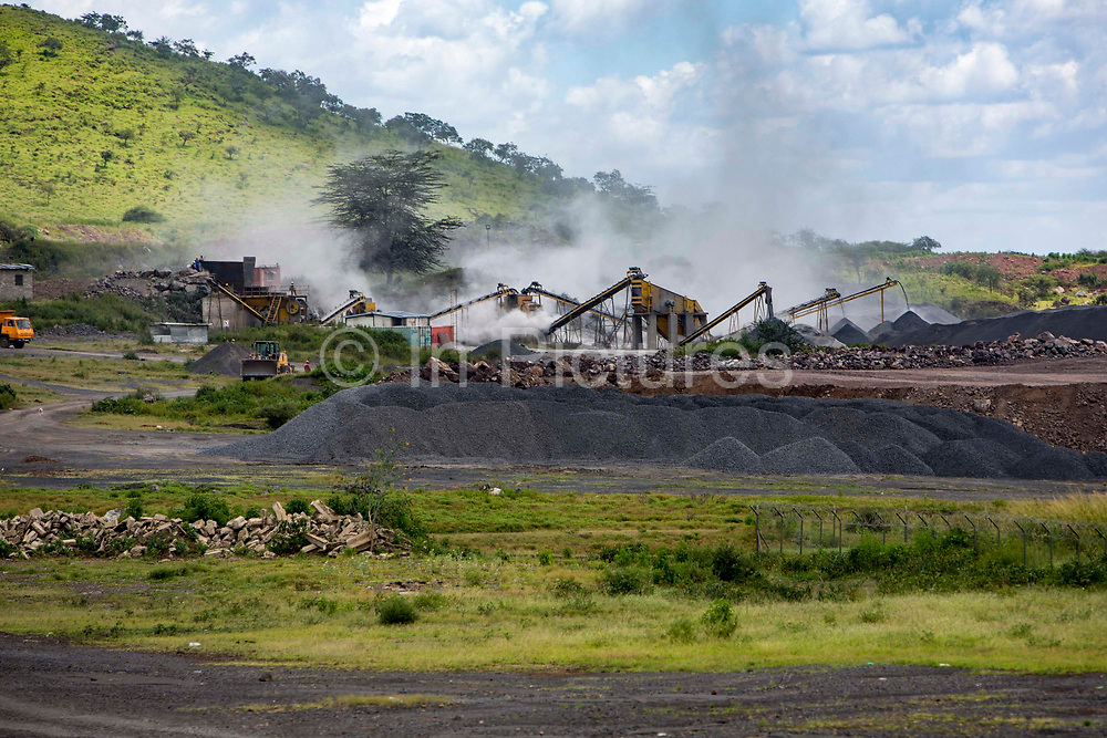 Dust clouds gather above a working gravel quarry on the outskirts of Mbulu, Manyara district, Tanzania.  The gravel is used mostly for new roads that are being built in Africa.