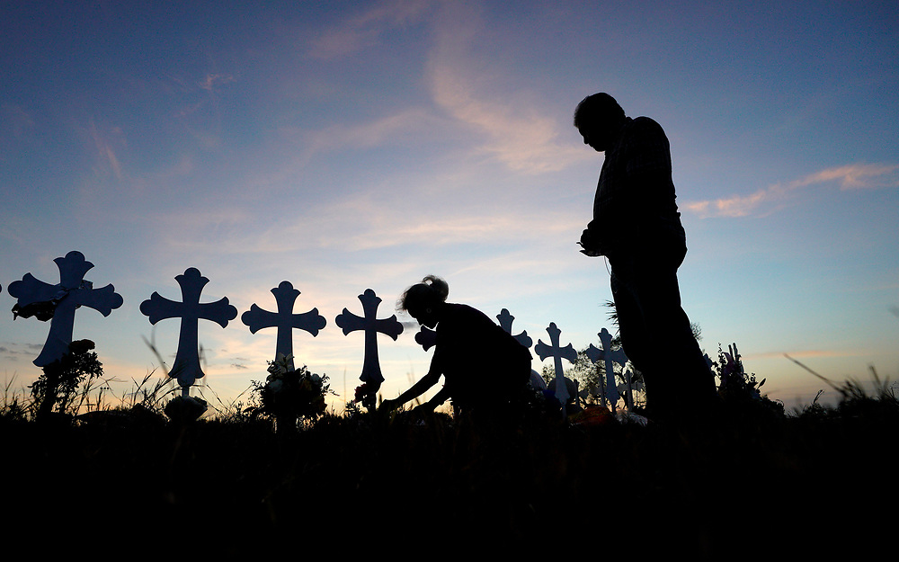 Judy Green places tiny American flags along a row of crosses as her husband Rod watches near the site of the shooting at the First Baptist Church of Sutherland Springs, Texas, U.S. November 7, 2017.  REUTERS/Rick Wilking