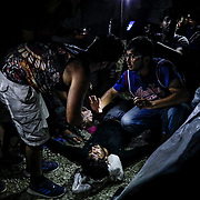 A refugee is resuscitated after experiencing a seizure from tear gas fired by Greek police during clashes with refugees hours after a fire inside of Moria camp. At least one person was killed by a fire as many refugees and migrants remain trapped in squalid living conditions at the camp on Lesvos Island in Greece onSunday, September 29, 2019. Credit: Byron Smith