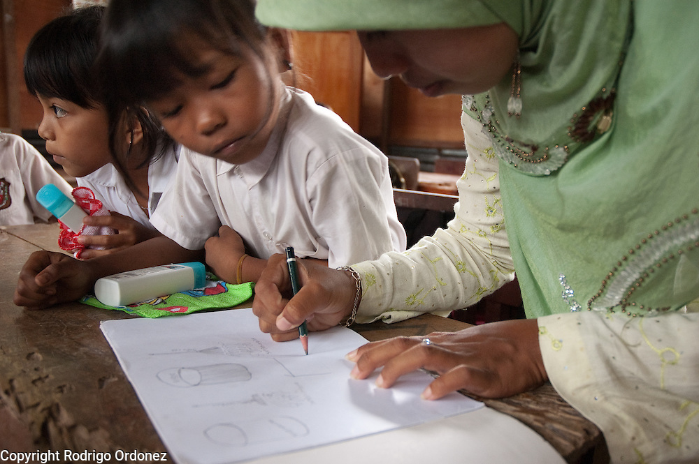 A teacher assists students at Elementary School 14 in Sungai Geringging during an exercise about the importance of hygiene and hand washing conducted by Save the Children in the aftermath of the West Sumatra earthquake.