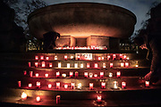 """People gather at  a makeshift memorial in Berlin, Germany, January 17,  2021. The memorial is part of the initiative  """"Corona-Tote sichtbar machen"""" (lit. Make corona deaths visible) by Christian Y. Schmidt and Veronika Radulovic,  since December 6, 2020, people gather at the fountain of Arnswalder Platz every Sunday at 16:00, light candles and place placards with the current death toll reported in Germany at the time. The death toll in Germany by variouse sources revolved around 47,000."""
