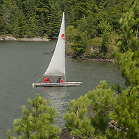 Sailors navigate a small boat similar to a Laser on Lake of the Woods, near Kenora, Ontario, Canada.