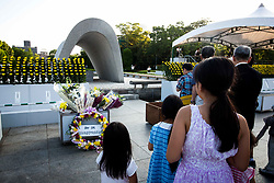 August 6, 2017 - Hiroshima, Hiroshima Prefecture, Japan - Visitors lays flowers and pray for the atomic bomb victims in front of the cenotaph at the Hiroshima Peace Memorial Park in Hiroshima, western Japan, Sunday, August 6, 2017. (Photo: Richard Atrero de Guzman/NURPhoto) (Credit Image: © Richard Atrero De Guzman/NurPhoto via ZUMA Press)