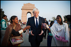 London Mayor Boris Johnson is chased by street vendors at India Gate in New Delhi, on the first of a six-day tour of India, where he will be trying to persuade Indian businesses to invest in London, Sunday November 25, 2012. Photo by Andrew Parsons / Parsons Media