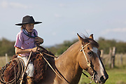 Young boy Gaucho cowboy Brazilian riding a horse. Working Gaucho Fazenda in Rio Grande do Sul, Brazil.