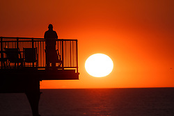 © Licensed to London News Pictures. 14/07/2019. Aberystwyth, UK.<br /> People silhouetted against the orange colour of the sunset as they stand on the seaside pier in Aberystwyth at the end of a warm summers day in west Wales. Photo credit: Keith Morris/LNP