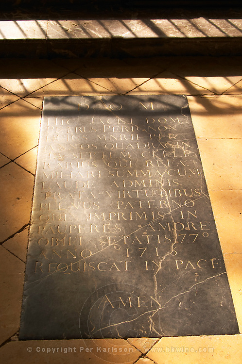 The tomb grave in a church of the monk Dom Pierre Perignon (the father of champagne) is buried, cellar master in the monastery Abbey (1639-1715). Rays of sunshine on the stone floor. Latin inscription on his tomb stone ending in Amen, the village of Hautvillers in Vallee de la Marne, Champagne, Marne, Ardennes, France