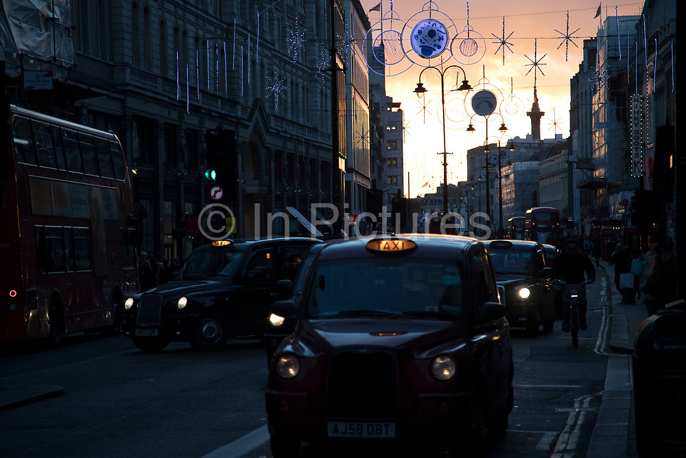 Street scene on Shaftesbury Avenue in central London as the sun sets and black taxi cabs pass in the low light in London, England, United Kingdom.