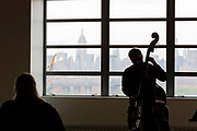 Brooklyn, NY - 7 May 2021. The Brooklyn Academy of Music (BAM) started a series of its first live concerts since the COVID pandemic lockdown in conjunction with the Silk Road Project at several sites in the Brooklyn Navy Yard. The 10-minute 1-to-1 concerts feature a single performer playing for a single audience member. Bassist Edward Perez plays in Building 77.