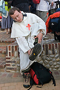 Little Walsingham, Norfolk, England, 06/04/2007..A priest removes his walking shoes after arriving at the Roman Catholic National Shrine of Our Lady. Pilgrims of various Christian denominations travel to Walsingham, one of Britain's oldest and most important centres of pilgrimage, to celebrate Easter.