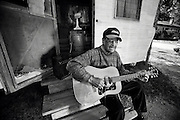 Blues guitarist Boo Hanks sits on the front steps of his trailer playing his acoustic guitar and singing.