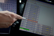 Detail of NATS air traffic controller's hand pointing to flight IDs on screen in control tower at Heathrow airport, London.