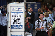 An Evening Standard newspaper headline announces the fury of London commuters' at a 3-day underground tube strike in September 2007. This is Victoria mainline station during a summer heatwave. It's a transport hub for tube lines, buses and overground train routes and we also see a stressed and exasperated-looking commuter walking past this kiosk with a Starbucks coffee container in hand, needing to get into work rather than take public transport. As a result of the industrial action, the busses are full so the quickest way of reaching one's destination is to walk.