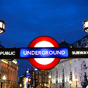Close-up of the traditional London Underground sign at Piccadilly Circus at night. Editorial use only.