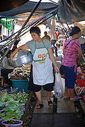 Mar. 24, 2009 -- A food vendor walks through the market in Samut Sangkhram. The market is the end of the Mahachai Rail line and is built right on the tracks. When the train comes through, vendors fold up their stalls and move them off the rails only to open them again after the train passes. The Mahachai Rail Line is a commuter line that runs from the Wong Wian Yai train station in the Thonburi section of Bangkok to the fishing port and market town of Samut Sakhon, which used to be known as Mahachai. An extension of the line runs from Baan Laem, near Samut Sakhon, to Samut Songkhram, another fishing port south of Samut Sakhon. Each stretch of the line takes about an hour.    Photo by Jack Kurtz