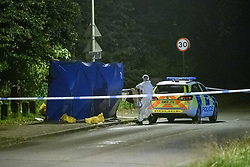 © Licensed to London News Pictures. 08/10/2021. Oxford, UK. A forensic investigator stands next to a privacy barrier alongside a Thames Valley Police car at the crime scene in Bayswater Road, Barton in Oxfordshire. Police were called just before 6:00pm today, Friday 08/10/2021, to reports of a man being stabbed, the victim, a man aged in his thirties, died of his injuries at the scene. Photo credit: Peter Manning/LNP