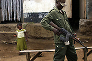 """A Young Tutsi rebel from CDNP (Congré National pour la Defense du Peuple) stands guard with a Kalashnikov in Bunagana, in March 17, 2008, where the commander of Laurent Nkunda, was reportedly arrested by the Congolese-Rwandan joint forces in January, 2009. After Nkunda's arrest, a peace treaty was signed, and there is an integration process with former CNDP militiamen and the government soldiers. In 2008 when the rebel fightings were intensified, average 14,245  rape cases a year were reported in the country. Women were raped in farms, jungles, homes, schools, and even inside IDP camps. Many of them suffered from physical condition called """"traumatic fistula"""" which were often caused by brutal gang rapes that left victims with no control over urination or defecation."""