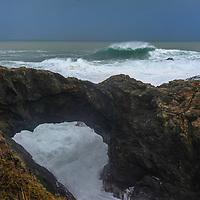 Pacific Ocean waves crash ashore through a natural bridge at Medocino Headlands State Park, near Mendocino, California.