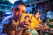 "19 AUGUST 2014 - BANGKOK, THAILAND:  Members of the Lehigh Leng Kaitoung Opera troupe put on their makeup before a performance at Chaomae Thapthim Shrine, a small Chinese shrine in a working class neighborhood of Bangkok. The performance was for Ghost Month. Chinese opera was once very popular in Thailand, where it is called ""Ngiew."" It is usually performed in the Teochew language. Millions of Chinese emigrated to Thailand (then Siam) in the 18th and 19th centuries and brought their culture with them. Recently the popularity of ngiew has faded as people turn to performances of opera on DVD or movies. There are still as many 30 Chinese opera troupes left in Bangkok and its environs. They are especially busy during Chinese New Year and Chinese holiday when they travel from Chinese temple to Chinese temple performing on stages they put up in streets near the temple, sometimes sleeping on hammocks they sling under their stage. Most of the Chinese operas from Bangkok travel to Malaysia for Ghost Month, leaving just a few to perform in Bangkok.            PHOTO BY JACK KURTZ"