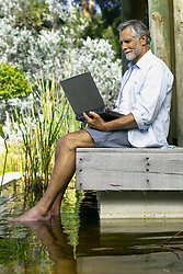 Dec. 05, 2012 - Man beside pool with computer (Credit Image: © Image Source/ZUMAPRESS.com)