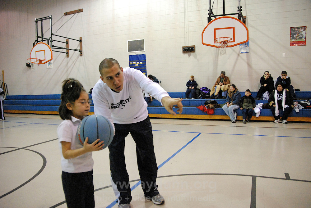 """USA, Chicago, IL, December 16, 2009.  Rob Castaneda shows a young player how to pass the ball in. Founded ten years ago by Rob and Amy Castaneda, """"Beyond the Ball"""" is a non-profit organization dedicated to giving kids and parents a healthy place to play together, whether it be in an after-school program or during an summer series of playground days, like last year's wildly successful """"Project Play."""" The predominantly working-class neighborhoods of Little Village and North Lawndale have no park, and little public space for families that is safe from the gang violence endemic to large US cities. Beyond the Ball's approach is personal, and takes a long-term view - both Rob and Amy are neighborhood residents, and have experienced first-hand the anger of gang members. The group arranges for school facilities to be open late, such as this gym at Josefa Ortiz de Dominguez Elementary, and welcomes student volunteers who also get credit from Chicago Public Schools for doing community service. Many of the teenagers working with """"Beyond the Ball"""" are comfortable as mentors, because they've been in the program before. It is easy to see the pride they take in teaching and taking responsibility for the younger kids, and how such a positive approach to neighborhood building can work. Photo for Hoy by Jay Dunn."""